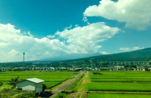 Mount Fuji behind the clouds seen from Tokaido Shinkansen